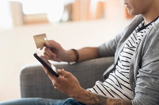 man shopping on mobile device at home holding credit card