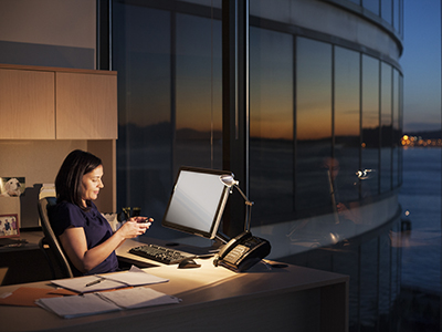 Female executive working at night with a computer in an office in Seattle, Washington, USA